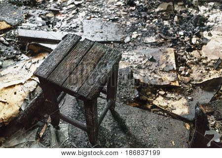Wooden charred chair in a burnt house, close-up, consequences of a fire concept, copy space