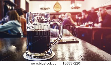 A large glass of dark beer on the background of the pub on a wooden table. Tinted glass.