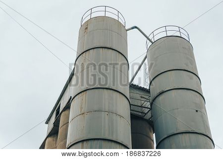 Steel round storage tanks or storage compartment at background of cloudy sky