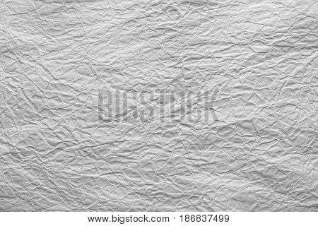 White crumpled sheet of paper. Grungy background texture with copy space for text or image.