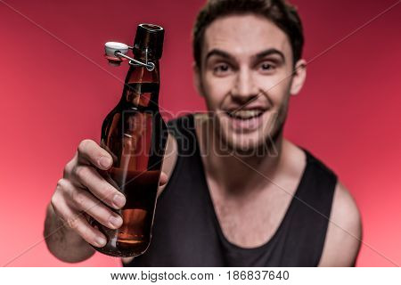 Close-up View Of Smiling Young Man Holding Beer Bottle