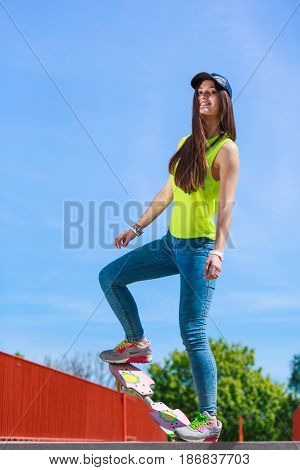 Summer sport and active lifestyle. Cool teenage girl in full length skater riding skateboard on the street. Outdoor.