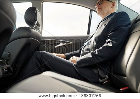 transport, business trip, safety and people concept - senior businessman driving on car back seat