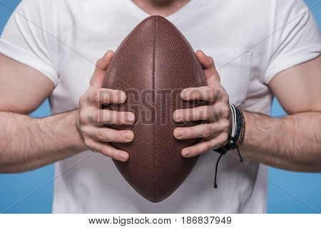 Close-up partial view of young man in white t-shirt holding rugby ball