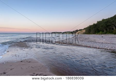 Small river goes into the sea. Steep bank on background. Baltic Sea coastline Latvia.