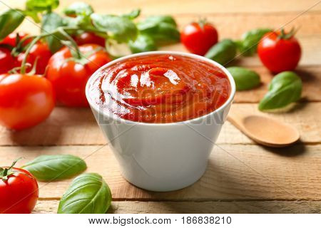 Delicious ketchup with basil and tomatoes on wooden background, closeup
