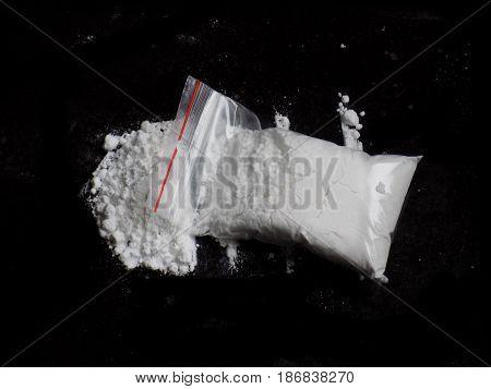 Cocaine drug powder bag and pile on black background