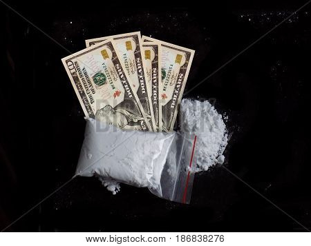 Cocaine drug powder pile and bag on dollar money bills