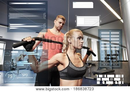 sport, fitness, exercising and people concept - young woman and personal trainer flexing muscles on cable gym machine over virtual charts