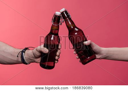 partial view of couple clinking bottles isolated on pink