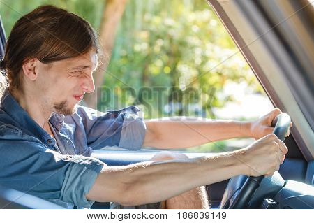 Traffic jam anger concept. Young furiously angry man wearing jeans shirt having long hair driving car and screaming at other drivers