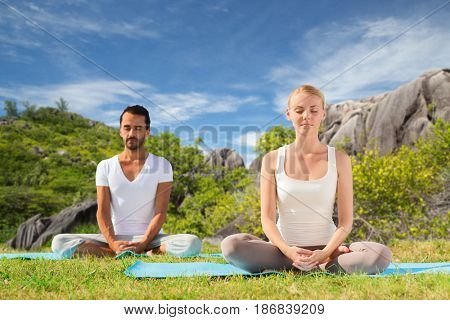 fitness, sport, meditation and people concept - happy couple doing yoga and meditating outdoors over natural background