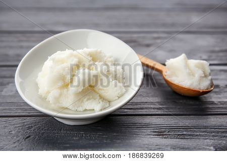 Shea butter in spoon and bowl on wooden background