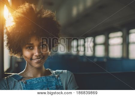 Young smiling beautiful black girl with curly afro hair sitting goes by suburban train attractive mixed teenage female on seat of empty electrical train with area for your text message or logo