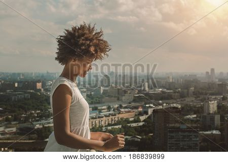 Young charming black Brazilian teen girl with beautiful curly afro hair in white dress standing on observation point very high and smiling sunny summer cityscape below in blurred background