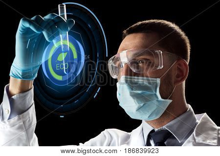 science, research and ecology concept - young scientist in safety glasses and face mask with test tube and virtual projection with eco icon