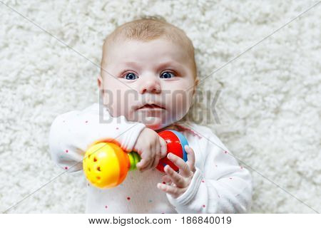 Cute adorable newborn baby playing with colorful rattle toy on white background. New born child, little girl looking at the camera. Family, new life, childhood, beginning concept. Baby learning grab