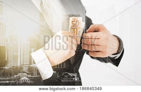 business, finances and people concept - close up of businessman with euro money over city with double exposure