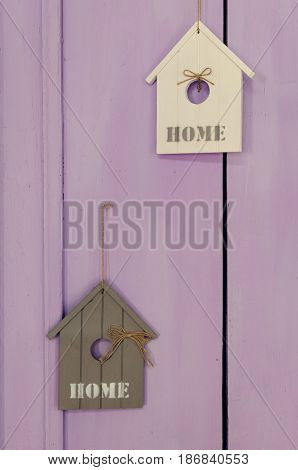 House interior decoration using little wooden houses with written word HOME on lavander background.