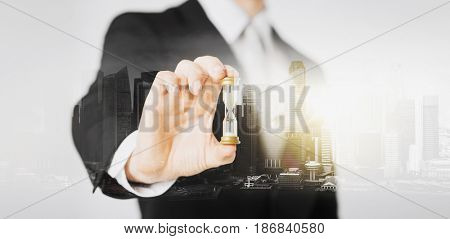 people, business and time concept - close up of businessman hand holding hourglass over city with double exposure