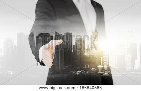 people, business and partnership concept - businessman hand ready for handshake over city with double exposure