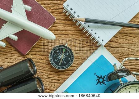 Travel planning concept with airplane passport compass binoculars pencil and paper note on wood table.