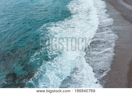 Soft and gentle blue sea waves foam in italy stone sand coast shore in summer daylight.