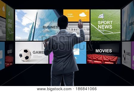 business, people, mass media and technology concept - businessman working with news applications virtual screen from back over black background