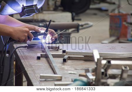 Soft focused picture of Worker is holding welding machine He is welding stainless steel pipe with argon mig - mag method in Industrial