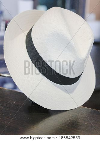 white hat with black band at an angle