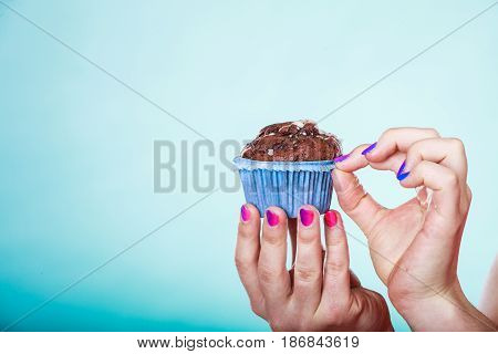 Delicious tasty sweet chocolate muffin in human hands. Confectionery food. Gluttony concept.