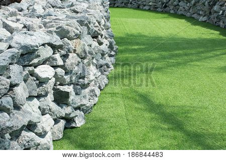 Soft focused picture of wall stone beside walkway and walkways cover by green artificial