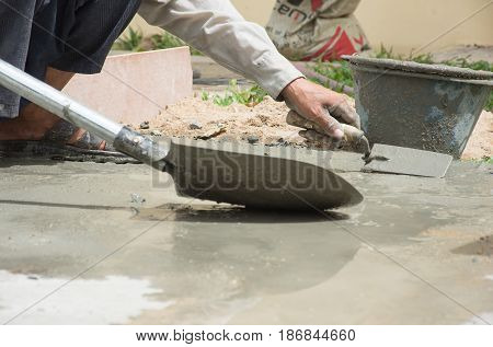 Hand of labour man using plastering and take the cement in to the bucket