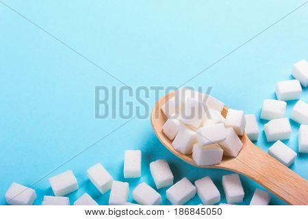 Sugar cubes in a wooden spoon with a blank space for copy paste text. On a blue background