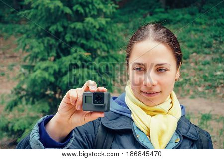 Young woman with action camera at green nature background