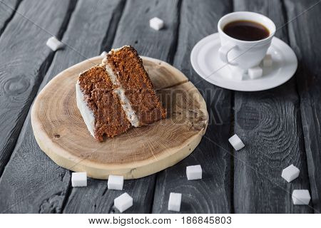 Piece of homemade cake and coffee on a black wooden table. Biscuit cake with black coffee. Lump sugar scattered on a table.