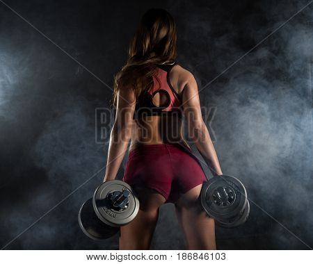 Fitness young woman in training with dumbbells, sporty muscular female brunette in smoke. girl wearing sports clothes working out with dumbbell over white backdrop