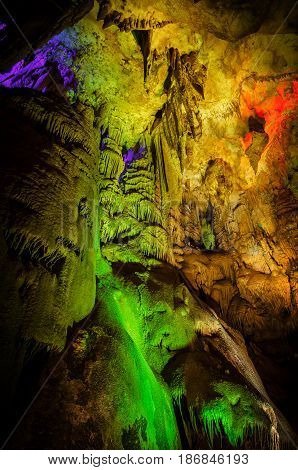Beautiful illuminated multicolored cave and stalactites from karst Prometheus Cave. Georgia.