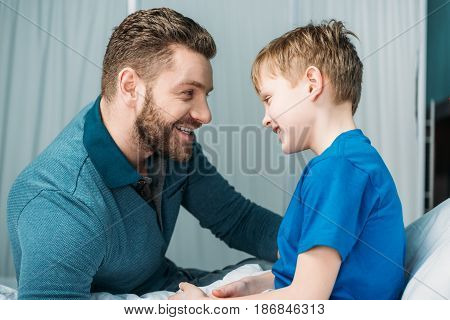 Side View Of Dad And Son Looking At Each Other In Hospital Chamber