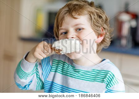 Little blond kid boy with curly hairs eating ice cream popsicle with chocolate at home or in kindergarten. Happy child is pleased about icecream, sweet dessert.