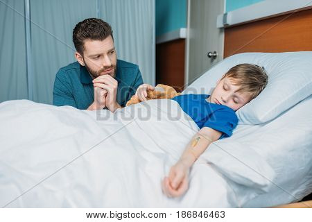 Portrait Of Pensive Dad Sitting Near Sick Son In Hospital Bed