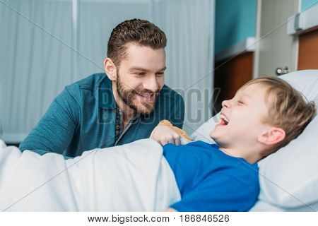 Happy Dad And Son Having Fun Together In Hospital Chamber