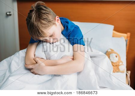Portrait Of Little Upset Boy Sitting On Hospital Bed