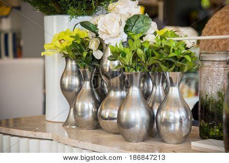 silver color aluminium vase with green plan.