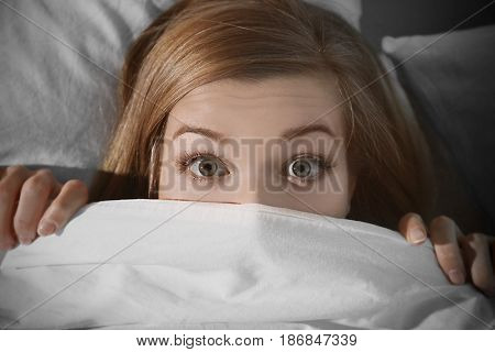 Young scared woman hiding under blanket while lying in bed at home