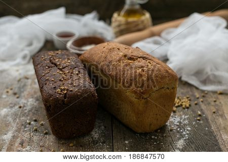 Close up view of fresh brown crispy loaf of bread lying on the wooden table sprinkled with flour. Little loaf of bread on the background.