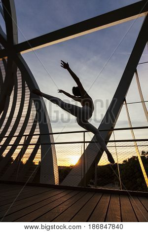 incredible high jump performed by a male dancer on a modern bridge at dawn