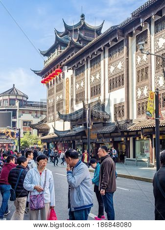 Shanghai, China - Nov 4, 2016: Along Fuyou Road - Area bustling with people and activities. The large store building is classical or traditional in Chinese architectural design.