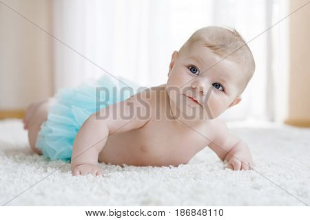 Adorable baby girl on white background wearing turquoise tutu skirt. Cute little child laughing and smiling. Happy carefree baby. Childhood, new life concept.