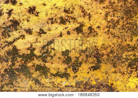 Rusty and corroded metal surface with peeled yellow paint. Grungy texture and background.